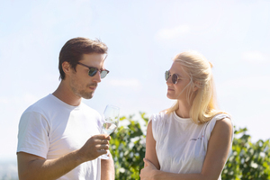 A woman and a man talk to each other with a glass of wine