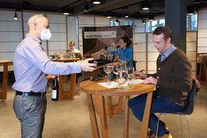 Gast bekommt Weißwein eingeschenkt