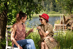 Two women talk to each other with a glass of wine