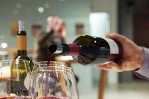 Gast bekommt Rotwein eingeschenkt