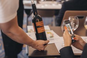 Kellner präsentiert Flasche